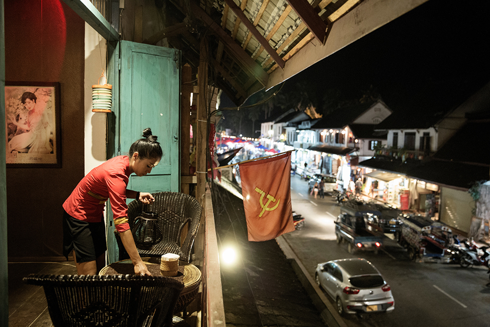 LAOS, NOVEMBER 2015. Luang Prabang, once considered a place for romantic dreamers, today is a magnet for expats in search of fortune in the new business of art and culture. A woman prepares a table at one of the many restaurants cropping up on the main promenade. Luang Prabang, Laos, 2015. @Giulio Di Sturco